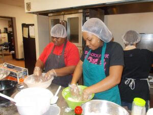 Site Supervisor Sequoia Bell and AIM High volunteer prepare food.