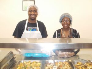 dscn2618Sam Greene, Site Supervisor serves food with one of the AIM Higher mentees