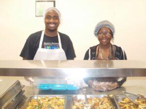 dscn2618Sam Greene, Site Supervisor serves food with one of the AIM Higher mentees